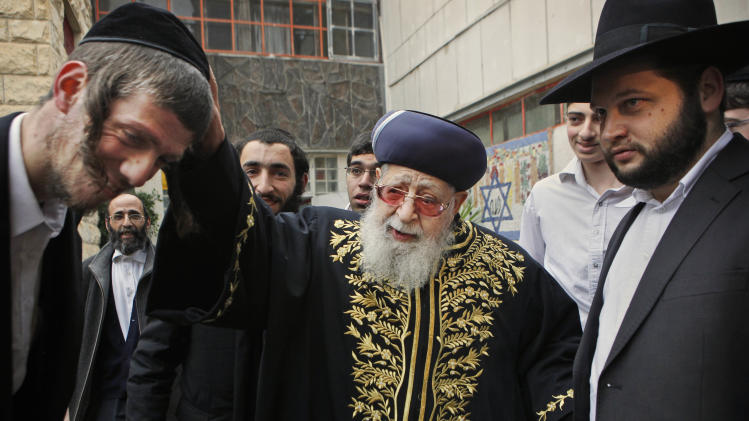 FILE - In this Feb. 10, 2009 file photo, Rabbi Ovadia Yosef, center, Jewish spiritual leader of Israel's Shas party, blesses a man after casting his ballot at a polling station in Jerusalem. An Israeli health official said Saturday Jan. 12, 2013, that influential Yosef has been hospitalized after feeling unwell. (AP Photo/Kevin Frayer, File)
