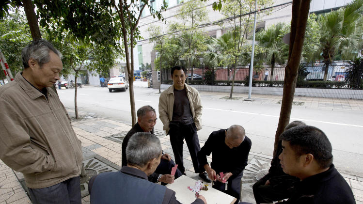 UPDATING THE CAPTION WHEN THE TRIAL STARTED - Chinese people play cards on the pavement near the Chengdu Intermediate People's Court in Chengdu in southwest China's Sichuan province Monday, Sept. 17, 2012. The trial of Wang Lijun, an ex-police chief at the center of China's worst political scandal in decades, started unexpectedly at the court Monday, a day earlier than the court had announced. At the height of his career, Wang led a police crackdown on the violent underworld in a sprawling metropolis, arresting hundreds of gangsters and government officials, some of whom were sentenced and executed in a matter of months. Now the former police chief is in the hands of the opaque Chinese justice he once brandished against others. (AP Photo/Andy Wong)