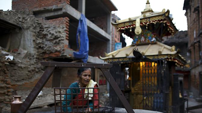 A woman fetches water from a well near collapsed house, a month after the April 25 earthquake  in Kathmandu