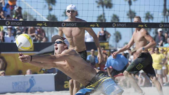 Tri Bourne dives for a dig as he and John Hyden played Casey Patterson and Jake Gibb during an AVP Championships beach volleyball match at Huntington Beach, Calif., on Sunday, Sept. 21, 2014. (AP Photo/The Orange County Register, Kyusung Gong)