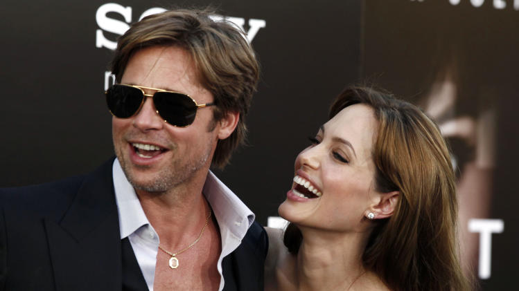 "FILE - In this Monday, July 19, 2010, file photo, cast member Angelina Jolie, right and Brad Pitt arrive at the premiere of ""Salt"" in Los Angeles. Jolie and Pitt were married Saturday, Aug. 23, 2014, in France, according to a spokesman for the couple. (AP Photo/Matt Sayles, File)"