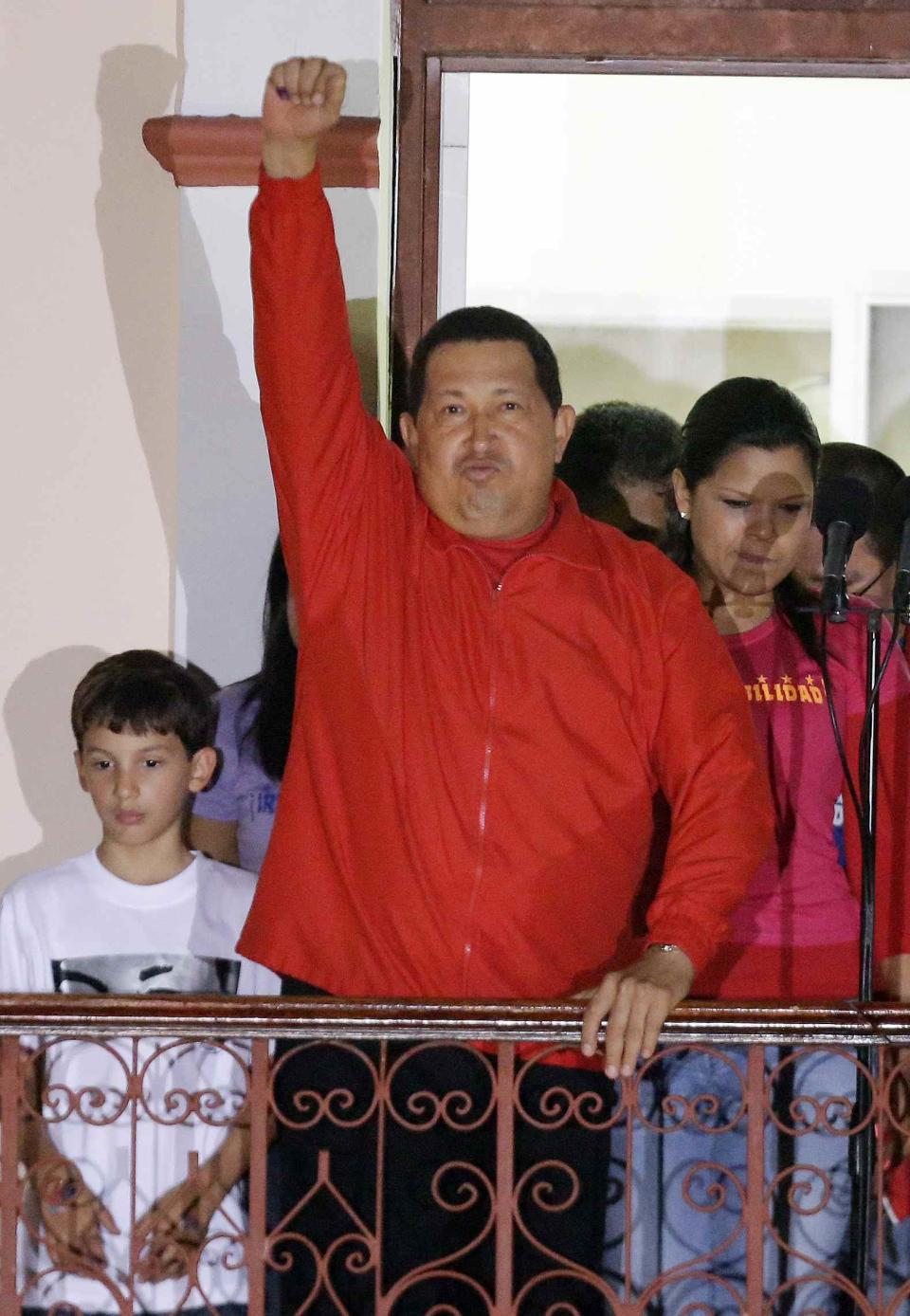 Venezuela's President Hugo Chavez greets his supporters at the Miraflores presidential palace balcony in Caracas, Venezuela, Sunday, Oct. 7, 2012.  Chavez won re-election and a new endorsement of his socialist project Sunday, surviving his closest race yet after a bitter campaign against opposition candidate Henrique Capriles.(AP Photo/Fernando Llano)
