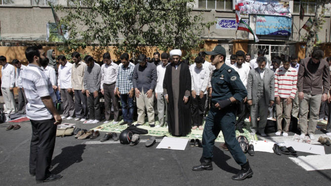 "Iranian demonstrators perform their noon prayer in front of the French Embassy in Tehran, Iran, Thursday, Sept. 20, 2012, as a police officer makes his way, during a protest the publication of caricatures of Islam's Prophet Muhammad by a French satirical weekly. Dozens of Iranian students and clerics gathered outside the embassy and chanted ""Death to France"" and ""Down with the U.S."" and burned the representation of the U.S. and Israeli flags Thursday. (AP Photo/Vahid Salemi)"