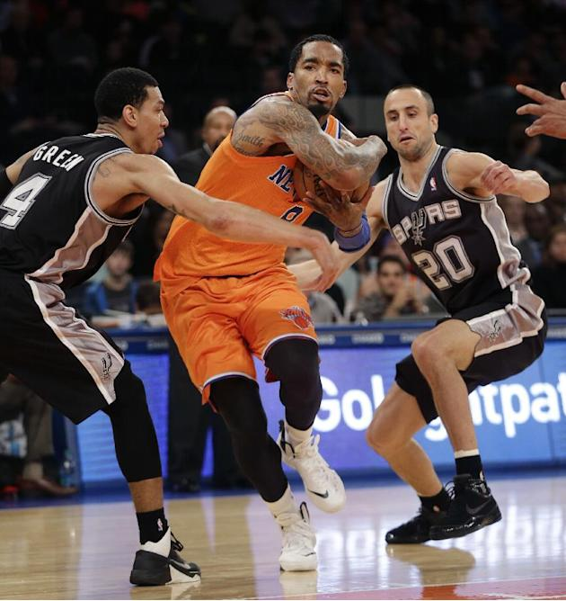 New York Knicks' J.R. Smith, center, drives through San Antonio Spurs' Danny Green, left, and Manu Ginobili during the second half of an NBA basketball game at Madison Square Garden, Sunday, Nov. 10,