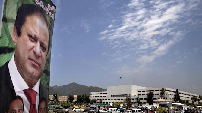 A banner with the portrait of Pakistan's upcoming Prime Minister Nawaz Sharif, is displayed near the National Assembly building, background, in Islamabad, Pakistan, Wednesday, June 5, 2013. Pakistan's parliament is set to elect Sharif as prime minister on Wednesday, completing a historic transition of power in the country's coup-riddled history. (AP Photo/Anjum Naveed)
