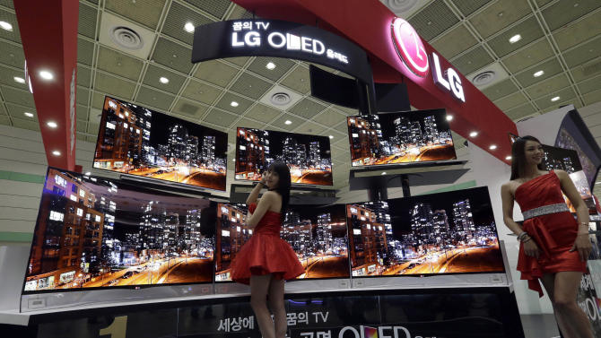 """FILE - In this May 21, 2013 file photo, South Korean models pose with LG Electronics' organic light-emitting diode (OLED) TVs during the World IT Show in Seoul, South Korea. Samsung Electronics Co., which is preparing for the global launch of the Galaxy S5 smartphone on April 11, 2014, said it is making """"concentrated efforts"""" to ensure its communications around the world respectfully portray women. Some of its promotions and corporate events in the past year were criticized as sexist and demeaning. The advertising of LG Electronics Inc. has also been under scrutiny in South Korea and abroad for its portrayal of women. (AP Photo/Lee Jin-man, File)"""