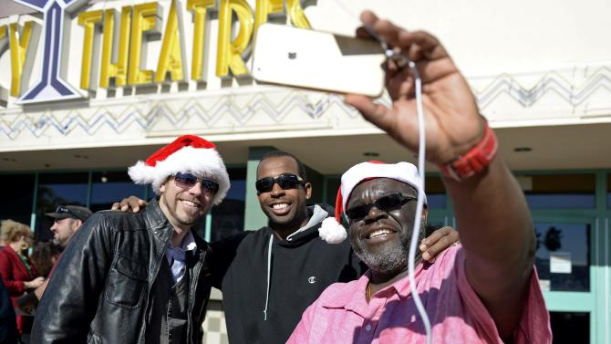 "Movie goers Carlos Royal, Ryan Bergstrom, and Khai Ky-Yeith pose for a ""selfie"" as they attend the Christmas Day screening of ""The Interview"" in the Van Nuys section of Los Angeles"