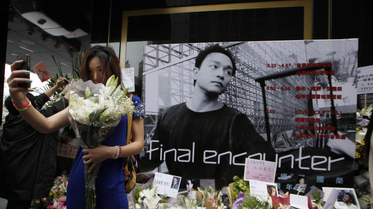 A fan takes picture of herself with a poster of the late Hong Kong actor-singer Leslie Cheung on an altar set up outside a hotel where Cheung jumped to his death, in Hong Kong Monday, April 1, 2013. Cheung's fans placed flowers to mark the 10th anniversary of the death of Hong Kong screen and singing legend Cheung. (AP Photo/Kin Cheung)