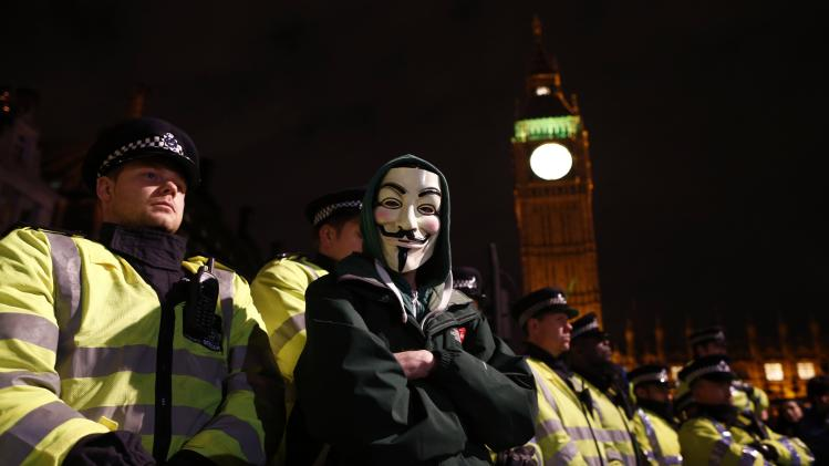 Protester wearing a Guy Fawkes mask stands in front of a line of riot police officers during a protest against budget cuts and energy prices in Westminster, central London