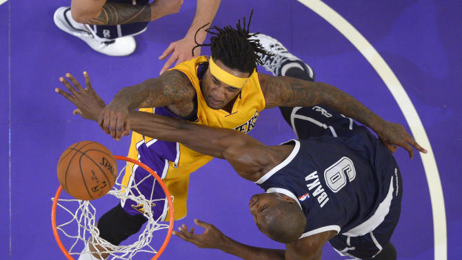 Los Angeles Lakers center Jordan Hill, left, puts up a shot as Oklahoma City Thunder forward Serge Ibaka, of Congo, defends during the second half of an NBA basketball game, Friday, Dec. 19, 2014, in Los Angeles.  The Thunder won 104-103. (AP Photo/Mark J. Terrill)