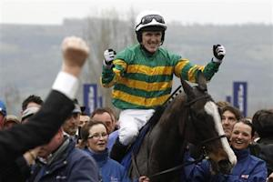 McCoy on Synchronised celebrates as he enters the unsaddling enclosure after winning The Gold Cup at the Cheltenham Festival horse racing meet in Gloucestershire