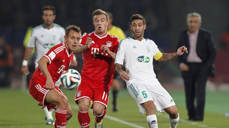 Mohsine Moutaouli of Morocco's Raja Casablanca fights for the ball with Xherdan Shaqiri (C) of Germany's Bayern Munich during their 2013 FIFA Club World Cup final soccer match at Marrakech stadium