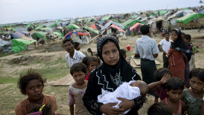 In this May 13, 2013 photo, an internally displaced Rohingya woman holds her newborn baby surrounded by children in the foreground of makeshift tents at a camp for Rohingya people in Sittwe, northwestern Rakhine State, Myanmar. Authorities in Myanmar's western Rakhine state have imposed a two-child limit for Muslim Rohingya families, a policy that does not apply to Buddhists in the area and comes amid accusations of ethnic cleansing in the aftermath of sectarian violence. (AP Photo/Gemunu Amarasinghe)