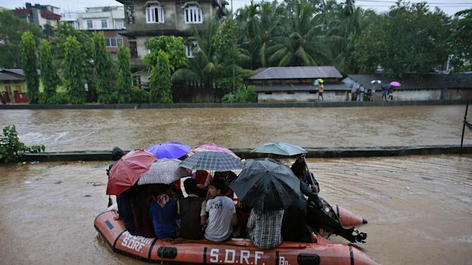 State Disaster Response Force personnel rescue people on a boat in a flooded area during heavy monsoon rains in Gauhati, Assam state, India, Monday, Sept. 22, 2014. Officials say relentless rains in parts of northeastern India have triggered landslides and flash floods, killing at least seven people. (AP Photo/Anupam Nath)
