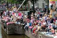 People gather on the banks of a canal waiting for the more than 80 boats participating in the boat parade during the annual gay parade in Amsterdam. Men in black leather shorts and little else, others in pink and silver body paint and drag queens in flamboyant dresses took to Amsterdam's canals Saturday