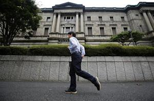 A pedestrian walks past the Bank of Japan headquarters in Tokyo