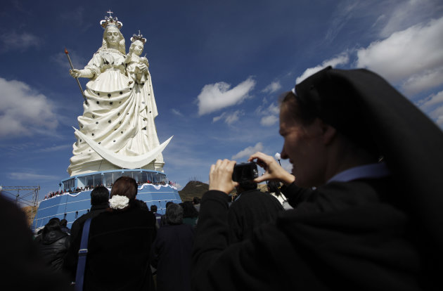 A nun takes pictures of a newly unveiled statue of the Virgin Mary holding a baby Jesus on Santa Barbara hill in the mining city of Oruro, Bolivia, Friday, Feb. 1, 2013. The 45 meter (147 feet) statue that took four years to build, known in Spanish as &quot;Virgen del Socavn,&quot; or the Virgin of the Tunnel, is Oruro&#39;s patron, venerated in particular by miners and folkloric Carnival dancers. (AP Photo/Juan Karita)