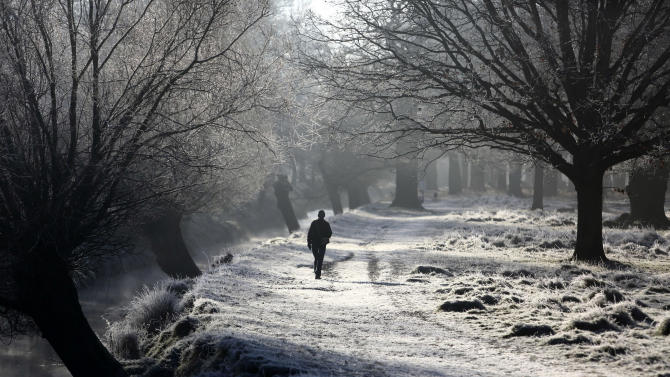 A pedestrian walks on a frost covered path in Richmond Park, southwest London, Monday, Dec. 29, 2014. Temperatures dipped below freezing overnight in many parts of the United Kingdom. (AP Photo/PA, Martin Keene) UNITED KINGDOM OUT, NO SALES, NO ARCHIVE