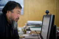 Chinese artist Ai Weiwei sits at a computer at his Beijing office in April 2012. The dissident artist has accused Chinese authorities of trying to &quot;crush him&quot; after he was barred from a hearing challenging a multi-million-dollar tax penalty against a firm he founded