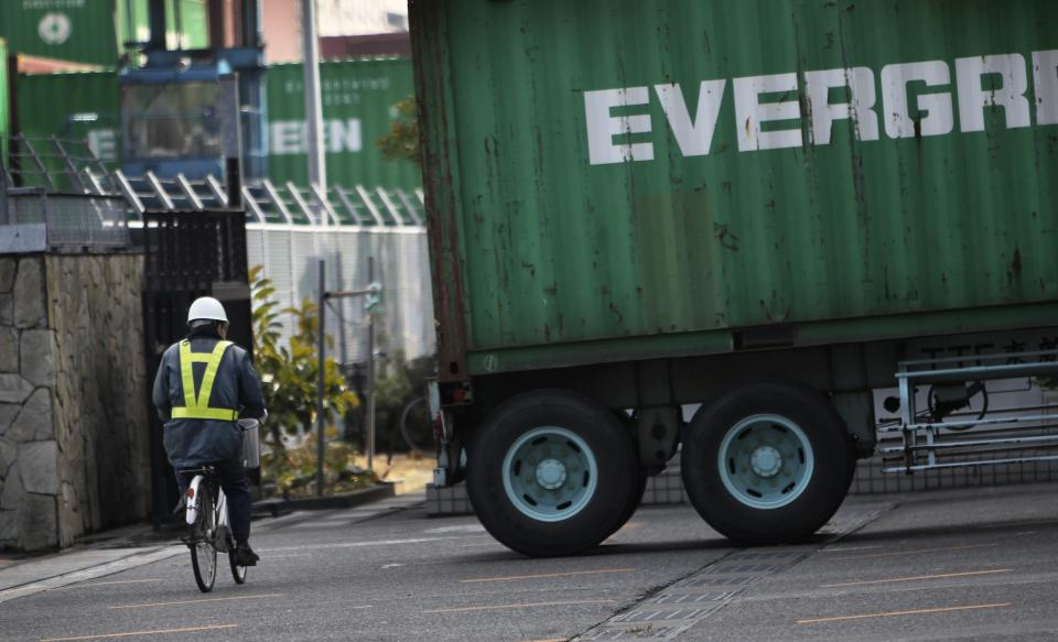 A security person pedals a bicycle at a container terminal in Tokyo, Wednesday, Jan. 25, 2012. Japan reported its first annual trade deficit since 1980 as it imported expensive energy to offset shortfalls caused by the devastating tsunami and manufacturers shifted production overseas to avoid the damage inflicted by the strong yen. (AP Photo/Junji Kurokawa)