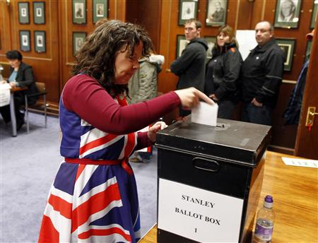A Falkland Islander wearing a dress with the Union Jack colours casts her vote at the Town Hall polling station in Stanley