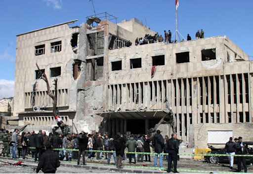 Syrian security officers gather in front the damaged building of the Syrian criminal security department, which was attacked by one of two explosions, in Damascus, Syria, on Saturday, March 17, 2012. Twin bombings struck government targets in the Syrian capital early Saturday, killing security forces and civilians and leaving pools of blood and carnage in the streets, according to state-run television. (AP Photo/Bassem Tellawi)