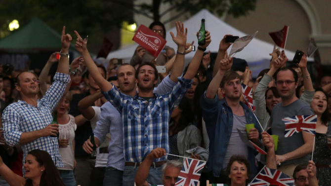 Visitors at a park celebrate during the live telecast of the Opening Ceremony of the 2012 Summer Olympics, Friday, July 27, 2012, in London. (AP Photo/Ng Han Guan)