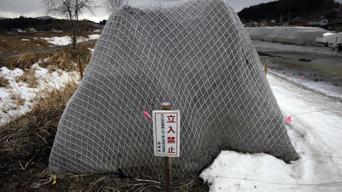 In this Sunday, March 3, 2013 photo, piles of radiation contaminated waste sit in a field in the abandoned town of Iitate, outside the exclusion zone surrounding the Fukushima Dai-ichi nuclear plant in Japan. The sign warns people to stay out because the area is reserved for radioactive waste storage. Two years after the triple calamities of earthquake, tsunami and nuclear disaster ravaged Japan's northeastern Pacific coast, radioactive and chemical contamination remains a threat as clean-up projects face troubles with organized crime and mishandling. (AP Photo/Greg Baker)