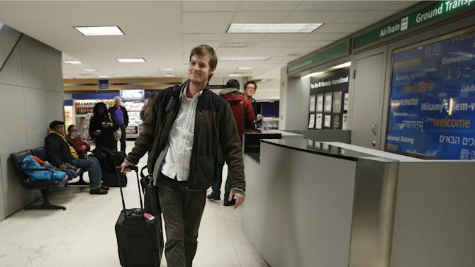 Jordan Houlton, of Toronto, walks through Kennedy International Airport en route to a connecting flight to Mexico after the Delta flight from Toronto he was on skidded off the runway into a snow bank, Sunday, Jan. 5, 2014, in New York. Houton said he slept through the incident. (AP Photo/Kathy Willens)
