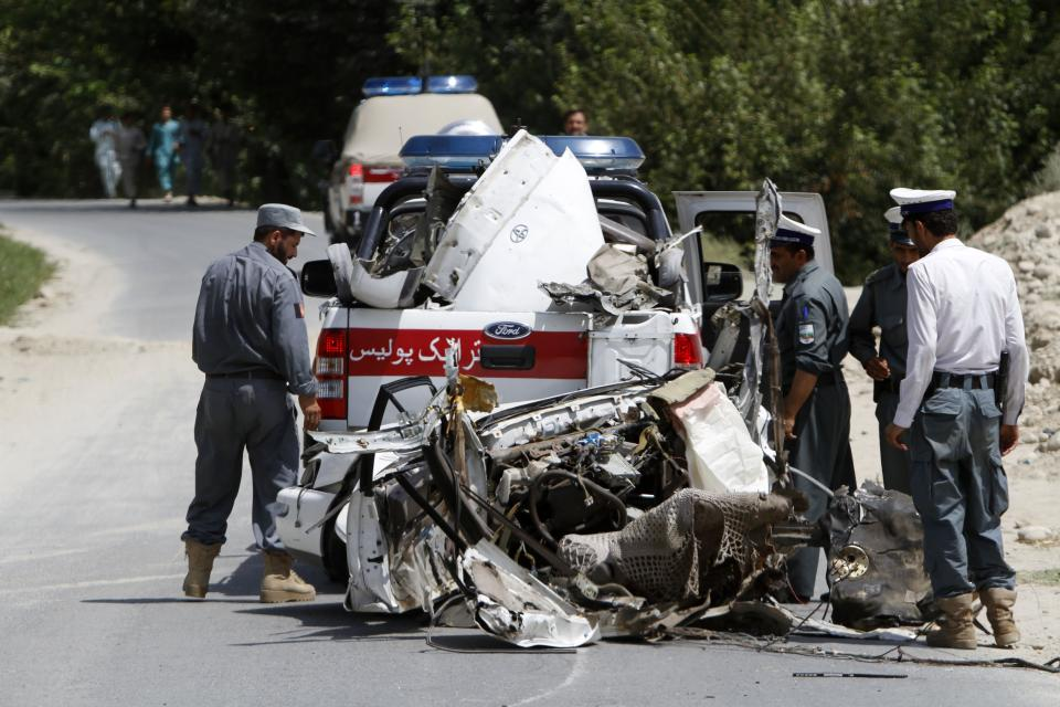 Afghan traffic police look at the wreckage of a vehicle after a roadside explosion on the outskirts of Laghman province east of Kabul, Afghanistan, Sunday, Aug. 12, 2012. A provincial spokesman says a roadside bomb has killed a district chief in eastern Afghanistan and three of his bodyguards. (AP Photo/Rahmat Gul)