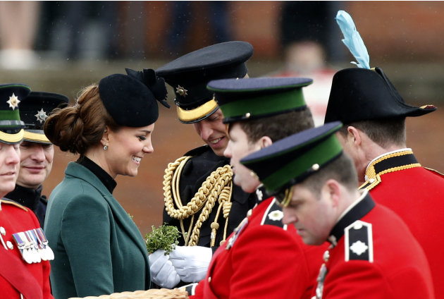 Britain's Kate Duchess of Cambridge, third left, stands with her husband Prince William, fourth left, before presenting traditional sprigs of shamrock to members of the 1st Battalion Irish Guards at t