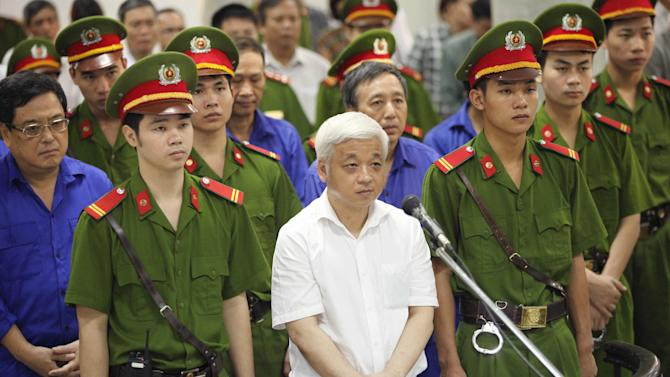 Nguyen Duc Kien, center, former vice chairman of the founding council of the Asia Commercial Bank (ACB), appears at the Hanoi People's Court in Hanoi, Vietnam, Monday, June 9, 2014. The court sentenced Kien, one of the country's richest men, to 30 years in prison on Monday after finding him guilty of financial crimes involving millions of dollars. Kien, a flamboyant businessman who also headed the Hanoi ACB football club, was arrested in 2012. The move was seen as part of the fallout of a power struggle among factions in the ruling Communist Party and allied business tycoons. (AP Photo/VNA Photo, Doan Tan) VIETNAM OUT