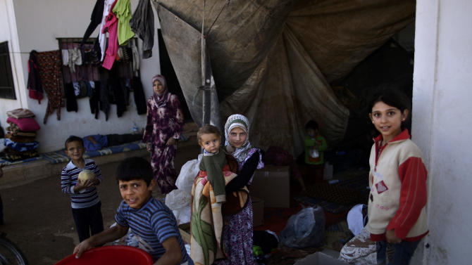 Syrian children, who fled their homes due to government shelling, look on, as they take refuge with their families at Bab Al-Salameh crossing border, hoping to cross to one of the refugee camps in Turkey, near the Syrian town of Azaz, Thursday, Sept. 13, 2012. (AP Photo/Muhammed Muheisen)