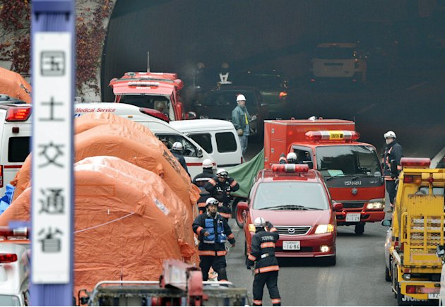 Firefighters work at the exit of the Sasago Tunnel on the Chuo Expressway in Otsuki, Yamanashi Prefecture, central Japan, Monday morning, Dec. 3, 2012. Concrete ceiling slabs fell onto moving vehicles