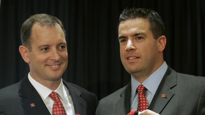 FILE - In this May 6, 2010 file photo, Mike Rice, left, is presented a jersey by Rutgers athletic director Tim Pernetti, right, after being introduced as the new men's head basketball coach at Rutgers during a news conference in Piscataway, N.J. A person familiar with the decision says Pernetti is out as Rutgers athletic director. The person spoke on condition of anonymity because an official announcement has not been made yet. The school will hold a press conference on campus at 1 p.m. Friday, April 5, 2013. Pernetti dismissed basketball coach Mike Rice Wednesday after a videotape aired showing him shoving, grabbing and throwing balls at players in practice and using gay slurs. The scandal has now cost Pernetti his job some five months after he didn't fire Rice when the video first became available.(AP Photo/Rich Schultz, File)