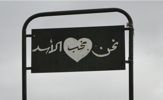 A panel that reads 'We love al-Assad' is seen at the police academy in Aleppo, after it was captured by Free Syrian Army fighters