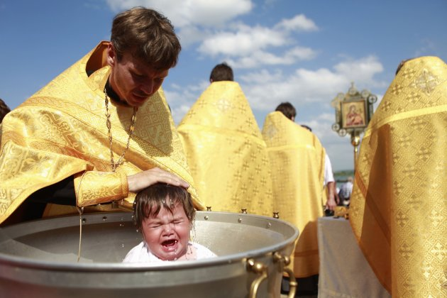 A priest baptises a child at Novopyatigorsk lake near Pyatigorsk