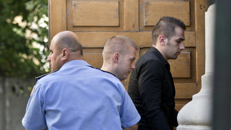 Eugen Darie, center, and Alexandru Bitu, right, two suspects charged with stealing paintings from a Dutch museum, enter a court building for a hearing in their trial in Bucharest, Romania, Tuesday, Sept. 10, 2013. Lawyers for Romanians charged with stealing paintings by Monet, Matisse and Picasso from a Dutch museum say their clients will plead guilty in the hopes of getting a reduced sentence. (AP Photo/Vadim Ghirda)