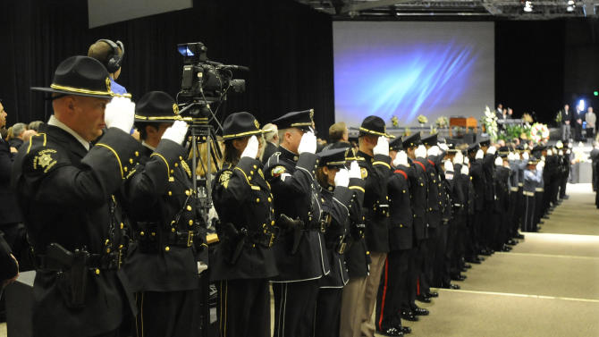 Law enforcement and corrections officers salute as the colors are brought to the stage at the memorial of Tom Clements during a public memorial for the chief executive of the Department of Corrections was held at New Life Church in Colorado Springs, Colo., on Monday, March 25, 2013. (AP Photo/The Gazette, Jerilee Bennett, Pool)