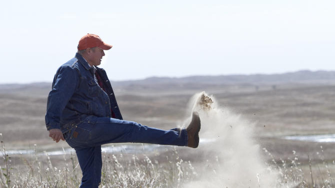 FILE - In this Sept. 29, 2011 file photo Atkinson, Neb., rancher Bruce Boettcher, who opposes the Keystone XL pipeline, kicks up sand on his land, to demonstrate the fragility of the sand hills near the planned route of the pipeline. The long-delayed Keystone XL oil pipeline cleared a major hurdle Friday, Jan. 31, 2014 as the U.S.State Department raised no major environmental objections to the controversial pipeline from Canada through the heart of the U.S. Republicans and some oil- and gas-producing states cheered, but the report further rankled environmentalists already at odds with President Barack Obama. (AP Photo/Nati Harnik, File)