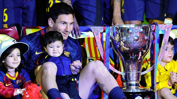 Lionel Messi holds son Thiago as they sit next to the La Liga trophy after FC Barcelona's 2-1 win over Real Valladolid CF. (Getty)