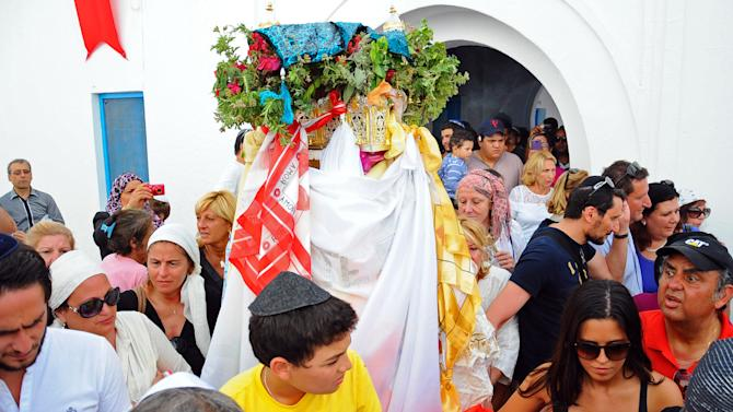 Jewish pilgrims gather for a procession at the Ghriba synagogue, during the annual Jewish pilgrimage in the resort of Djerba, Tunisia, Friday April 26, 2013.  They come to celebrate the annual rites at El-Ghriba, the oldest Jewish monument built in Africa more than 2,500 years ago.  On April 11, 2002 a deadly attack on the synagogue killed 21 people, including 14 German tourists.(AP Photo/Hassene Dridi)