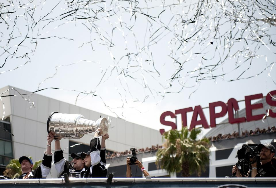 Los Angeles Kings players from left, Matt Greene, Anze Kopitar and Dustin Brown hold up the Stanley Cup during a parade and rally celebrating the team's NHL hockey Stanley Cup championship in Los Angeles, Thursday, June 14, 2012.  (AP Photo/Grant Hindsley)