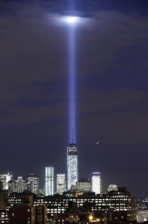 In this photo made with a long exposure, a test of the twin beams of the Tribute in Light intersect with still-under construction Tower One as they rise behind the building and above lower Manhattan, Monday, Sept. 9, 2013, in New York. The memorial, sponsored by the Municipal Art Society, will light the sky on the evening of Sept. 11, 2013, in honor of those who died in the Sept. 11, 2001, terror attacks on the United States. (AP Photo/Kathy Willens)