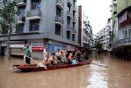 Residents use a boat to make their way along a flooded street in Chongqing, China. Flooding costs billions of dollars in Asia's region's cities and urban areas, but not nearly enough is being done to improve their defences, the Asian Development Bank said