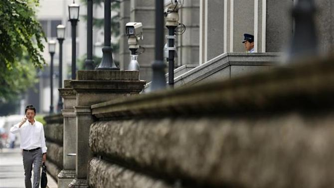 A pedestrian speaks on his mobile phone while walking past the Bank of Japan headquarters in Tokyo August 8, 2013. REUTERS/Yuya Shino/Files