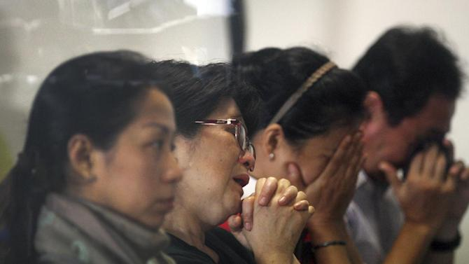 Relatives and next-of-kin of passengers on the AirAsia flight QZ8501 wait for the latest news on the search of the missing jetliner at Juanda International Airport in Surabaya, East Java, Indonesia, Monday, Dec. 29, 2014. Search planes and ships from several countries on Monday were scouring Indonesian waters over which the AirAsia jet disappeared, more than a day into the region's latest aviation mystery. The Flight 8501 vanished Sunday in airspace thick with storm clouds on its way from Surabaya, Indonesia, to Singapore. (AP Photo/Trisnadi Marjan)