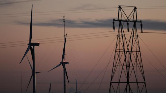 This Nov. 3, 2012 photo shows wind turbines, alongside an electrical tower, at the National Wind Technology Center, run by the U.S. Department of Energy, outside Boulder, Colo. The wind energy boom touted by President Barack Obama as a key to America's energy strategy has hit a wall in an election-year political dispute with Republican lawmakers over taxpayer support for renewable energy. (AP Photo/Brennan Linsley)