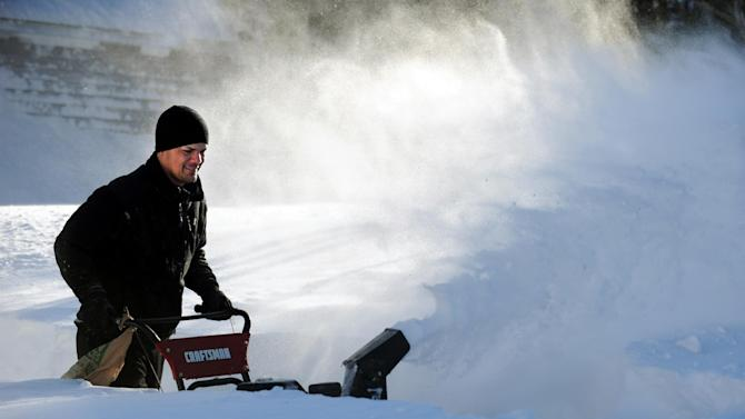 Tony Colon uses a snowblower to clear his driveway in Derby, Conn., as residents face massive snow removal, Saturday, Feb. 9, 2013, following a severe blizzard that dumped up to three feet of snow across the state. (AP Photo/The Connecticut Post, Autumn Driscoll) MANDATORY CREDIT