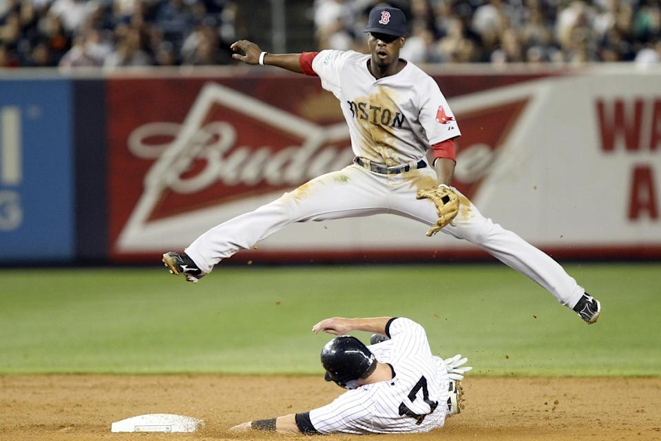 Boston Red Sox's Pedro Ciriaco jumps over New York Yankees' Jayson Nix as he turns a double play during the third inning of a baseball game at Yankee Stadium in New York, Sunday, July 29, 2012. (AP Photo/Seth Wenig)